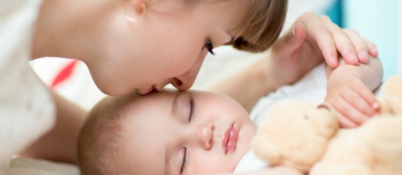 MOT female kissing sleeping baby